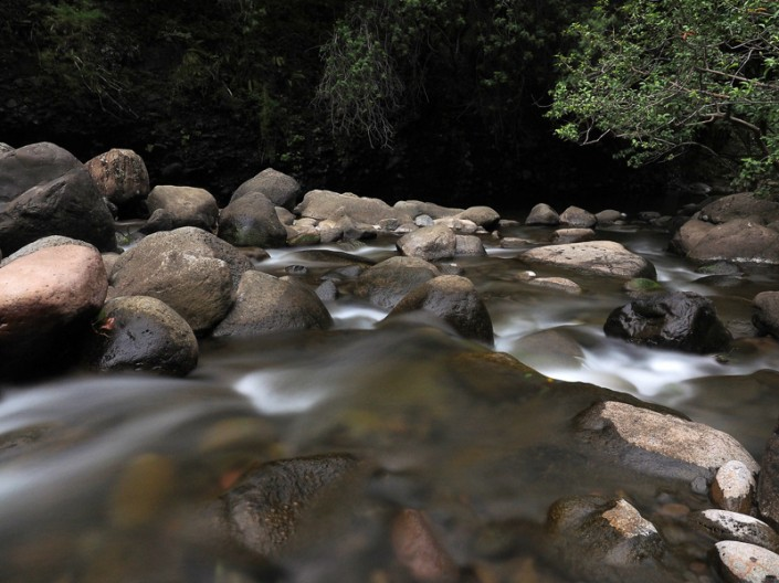 An image of clear rushing water over boulders at Iao Stream, Maui, Hawaii