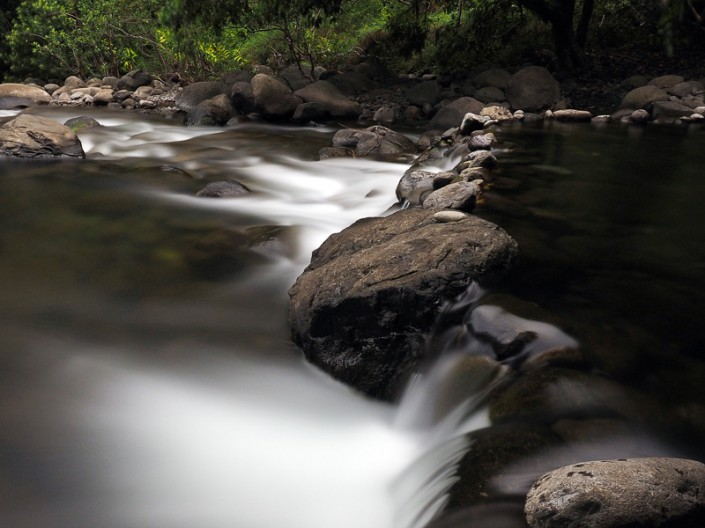 A view of white silky water flowing over rocks at Iao Stream