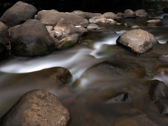 A view of large boulders and flowing water at Iao Stream