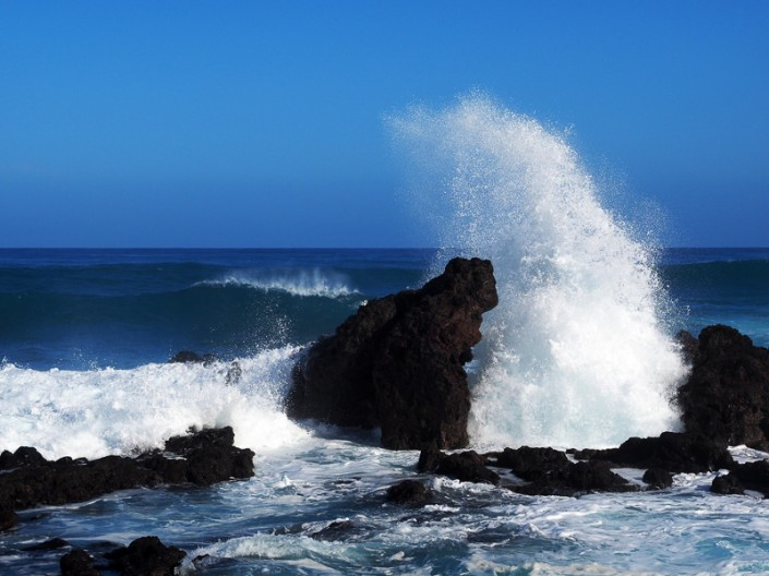 A wave crashing on a large lave rock at Hookipa Beach, Maui, Hawaii