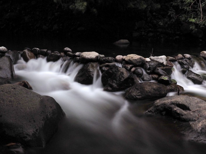 A view of Maui's Iao Stream with rapid rushing over rocks