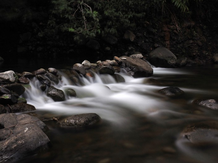 Water flowing over a man made rock wall at Iao Stream in Iao Valley State Park, Maui, Hawaii