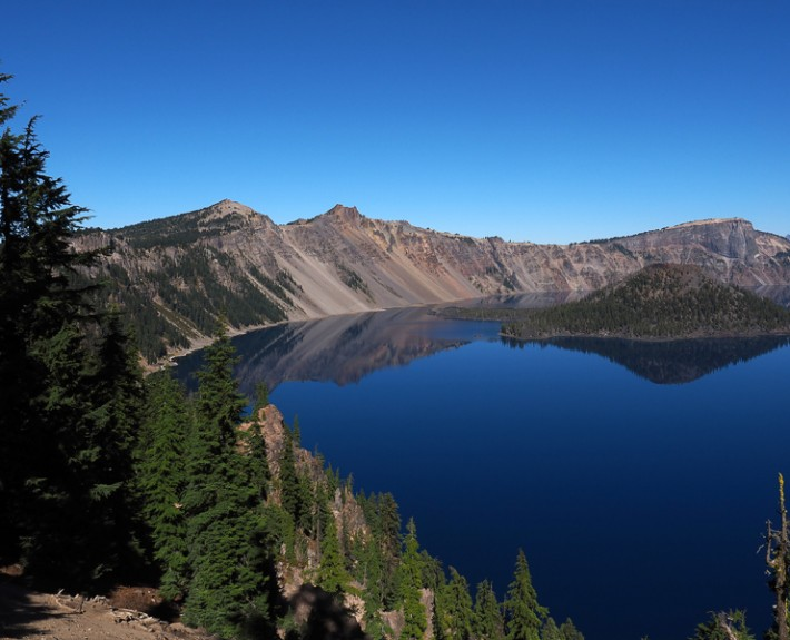 A view of calm, reflective, cobalt blue waters inside Crater Lake