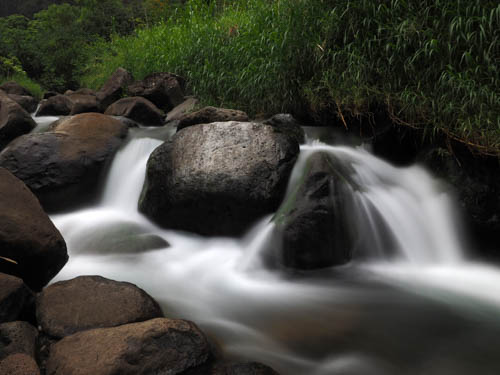 beautiful soft, silky, milky white wate cascades over boulders at Iao Stream